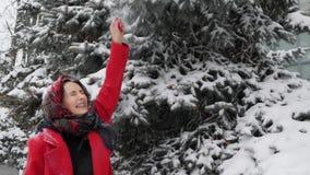 红色外套戏剧的笑美丽的年轻白种人的妇女与雪和圣诞树户外微笑和 雪在attrac落 股票录像