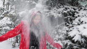 红色外套戏剧的笑美丽的年轻白种人的妇女与雪和圣诞树户外微笑和 ??attrac? 股票录像