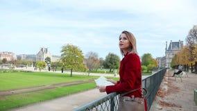 红色外套的女孩有地图的在巴黎 股票视频