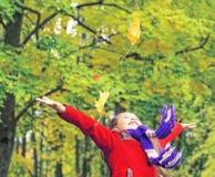 红色外套的小笑的俏丽的女孩在秋天公园投掷黄色叶子 免版税图库摄影