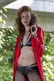 红色外套的枪妇女 免版税库存图片