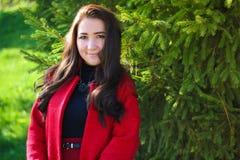 红色外套的美丽的亚裔妇女 免版税图库摄影