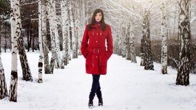 红色外套的美丽的端庄的妇女 免版税图库摄影
