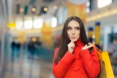 红色外套购物的好奇女孩在购物中心 免版税库存图片