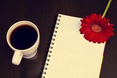 红色大丁草花和笔记本在木书桌上 免版税图库摄影