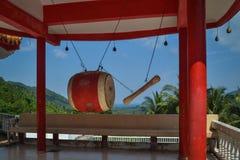 红色大鼓用垂悬在小山的上面的棍子在金佛教寺庙的 免版税库存图片