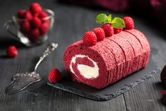 红色天鹅绒海绵卷蛋糕用在黑暗的背景的新鲜的莓 库存图片
