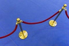 红色天鹅绒绳索和一张蓝色地毯 免版税库存图片