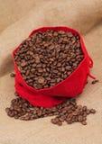 红色天鹅绒囊用咖啡豆 库存照片