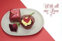 红色天鹅绒杯形蛋糕、礼物和玫瑰色芽餐桌设置与爱消息为情人节 库存照片