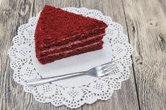 红色天鹅绒蛋糕新鲜美甜片断,在一块白色餐巾和一把点心叉子在木背景 库存图片