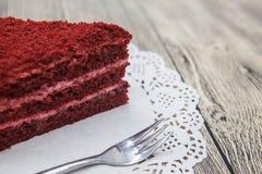 红色天鹅绒蛋糕新鲜美甜片断,在一块白色餐巾和一把点心叉子在木背景 库存照片