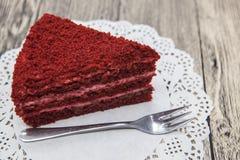 红色天鹅绒蛋糕新鲜美甜片断,在一块白色餐巾和一把点心叉子在木背景 免版税库存照片