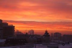 红色太阳升起在冬天城市 免版税库存照片
