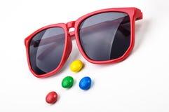 红色太阳镜和许多五颜六色的圆的candys 库存照片