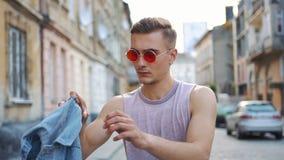红色太阳镜的人承担他的牛仔裤背心走沿街道的 股票视频