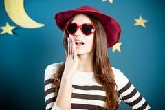 红色太阳镜的俏丽的女孩有纸月亮的和 库存照片
