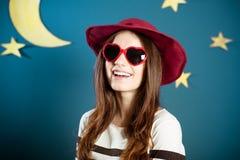红色太阳镜的俏丽的女孩有纸月亮的和 免版税库存照片