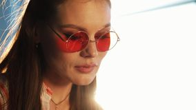 红色太阳镜的年轻可爱的妇女使用有触摸屏幕的片剂计算机在咖啡馆 美丽的女孩在机场或 影视素材