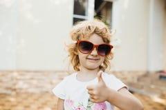 红色太阳镜的逗人喜爱的小女孩 图库摄影