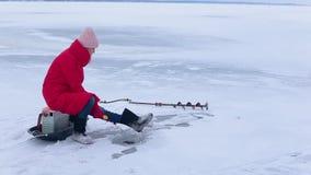 红色夹克和毛毡起动的年轻美女坐冰并且抓在孔的鱼与帮助冬天钓鱼竿 股票视频