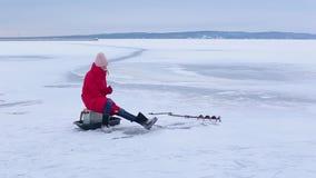 红色夹克和毛毡起动的年轻美女坐冰并且抓在孔的鱼与帮助冬天钓鱼竿 影视素材