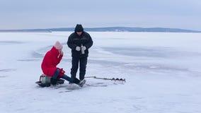 红色夹克和毛毡起动的美丽的女渔翁抓与帮助冬天钓鱼竿的鱼 股票录像