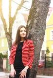 红色夹克和黑礼服的年轻可爱的妇女在街道上 免版税库存图片