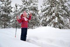 红色夹克滑雪的女孩在多雪的森林里 免版税库存图片