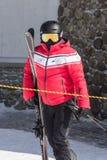 红色夹克的一个滑雪者拿着他的雪板和滑雪杆 库存照片