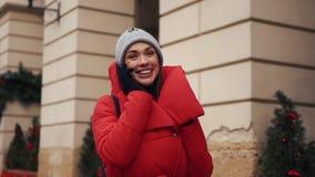 红色夹克的俏丽的女孩在站立在街道上的智能手机谈话在一个明亮的冬日 股票录像