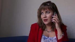 红色夹克的可爱的妇女使用在任何地方坐期间的手机 股票视频
