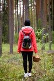 红色夹克的少妇享受自然的在森林拉脱维亚里 免版税库存照片