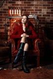 红色夹克的年轻和可爱的白肤金发的妇女在皮革扶手椅子,背景难看的东西生锈的墙壁坐 免版税库存图片