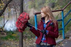 红色夹克的时髦的金发碧眼的女人打开伞 免版税库存图片