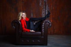 红色夹克的年轻和可爱的白肤金发的妇女在皮革扶手椅子,在扶手的脚坐 免版税库存照片