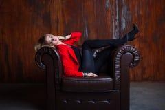 红色夹克的年轻和可爱的白肤金发的妇女在皮革扶手椅子,在扶手的脚坐 库存照片