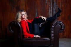 红色夹克的年轻和可爱的白肤金发的妇女在皮革扶手椅子,在扶手的脚坐 免版税图库摄影
