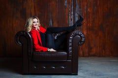 红色夹克的年轻和可爱的白肤金发的妇女在皮革扶手椅子,在扶手的脚坐 免版税库存图片