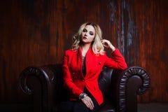 红色夹克的年轻和可爱的白肤金发的妇女在皮革扶手椅子,背景难看的东西生锈的墙壁坐 库存照片