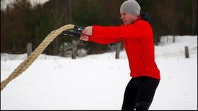 红色夹克训练的年轻肌肉人与争斗绳索冬天和雪慢动作 户外健身锻炼 股票录像