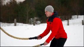 红色夹克训练的年轻肌肉人与争斗绳索冬天和雪慢动作 户外健身锻炼 股票视频