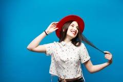 红色女性呢帽 在蓝色背景 愉快和新鲜 免版税库存图片