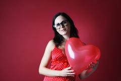红色女用贴身内衣裤的性感的妇女有气球形状心脏的在红色背景情人节 库存照片