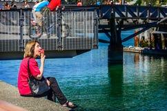 红色女衬衫的妇女吃红色冰淇凌的 免版税库存图片