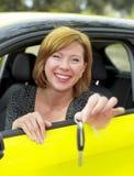 红色她20s或30s坐的头发愉快和微笑的女孩骄傲在把握和显示汽车关键的驾驶席在新的汽车buyin 库存照片