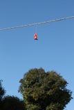 红色妇女穿上鞋子垂悬在一根电导线 免版税库存图片