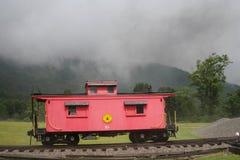 红色守车有雾的山 免版税库存图片