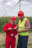 红色安全帽的监督员谈话与工作者在风力场 免版税库存图片