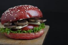 红色小圆面包和新鲜的芝麻在被烘烤的小圆面包、水多的酥脆蘑菇汉堡小圆面包、健康膳食午餐的和晚餐 图库摄影